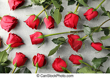Composition with red roses on grey background, top view