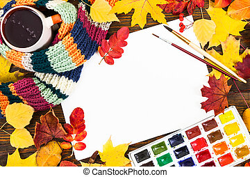 Composition with sheet of white paper, paints, brushes and autumn colorful leaves.