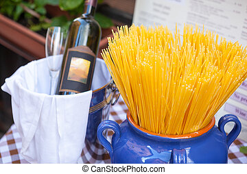 Composition with Spaghetti in vase and bottle of red wine.