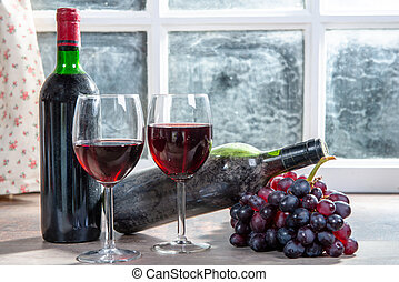 Composition with two wineglasses, grapes and bottle of red wine