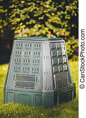 compost bin on green grass and foliage background
