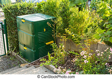 Compost maker bin for  recycle kitchen, yard and garden scraps in small garden.