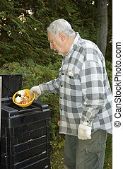 To protect the world from pollution this elderly man puts kitchen scraps into the bin and reuse the compost on his garden