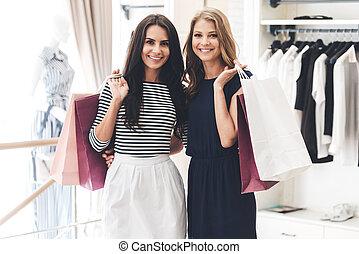 compras, con, amigo, es, puro, pleasure!, dos, mujeres hermosas, con, bolsas de compras, mirar cámara del juez, con, sonrisa, mientras, posición, en, el, tienda de ropa