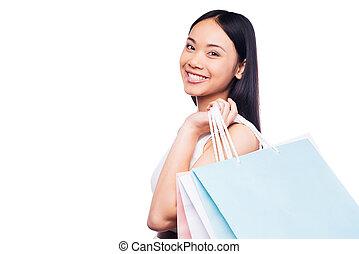 compras, es, el, mejor, hembra, occupation!, vista lateral, de, hermoso, joven, mujer asiática, en, vestido bonito, mirar cámara del juez, y, tenencia, bolsas de compras, mientras, posición, contra, fondo blanco