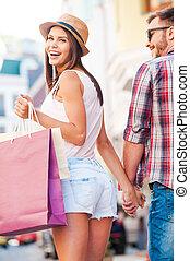 compras, juntos, es, fun!, vista trasera, de, hermoso, joven, par cariñoso, ambulante, por, el, calle, mientras, mujer hermosa, proceso de llevar, bolsas de compras, y, mirar hombro