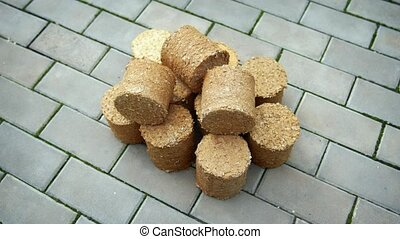 Round pellets of biofuel for home heating, made from compressed and dried sawdust and shredded paper, stacked on the floor.