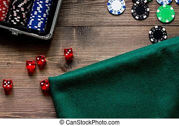 Compulsive gambling. Poker chips and the dice nearby green gambling cloth on wooden table top view copyspace
