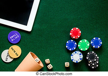 Compulsive gambling. Poker chips and the dice nearby tablet on green table top view copyspace
