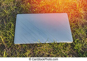computador portatil, estar tendido en el césped, en, un, soleado, día de verano