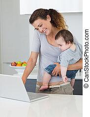 computador portatil, mientras, proceso de llevar, madre, bebé, utilizar, cocina