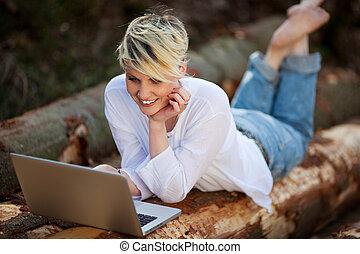 computador portatil, mujer, troncos, acostado