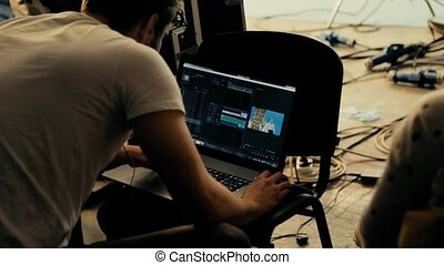 The team works on the laptop. A group of professionals are working on a big film in a video studio. Professional equipment and well-coordinated team work.