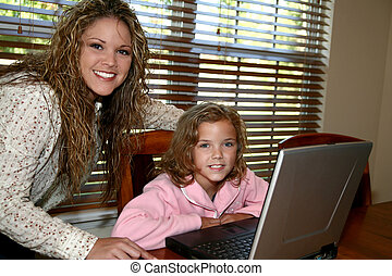 Computer at Home - Beautiful Mother and Daughter working on...
