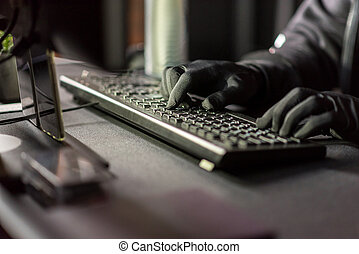 Close up arms of hacker typing on keyboard while stealing information from digital device