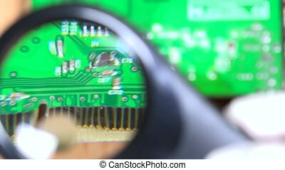 Computer card detail looking with magnifying glass at pc repair service