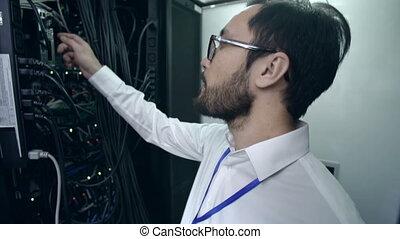 Computer Center - Tilt up of scientific worker disconnecting...