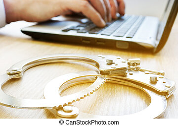 Computer crime. Man with laptop and handcuffs. Investigation...