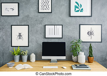 Computer desktop on wooden desk with plants in grey workspace interior with posters. Real photo