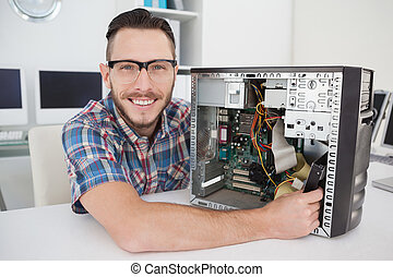 Computer engineer working on broken console smiling at camera