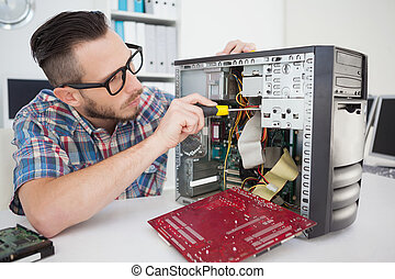 Computer engineer working on broken console with screwdriver...