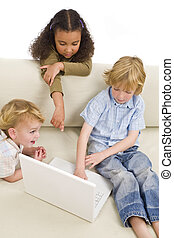 Computer Generation - Three young children using a laptop...