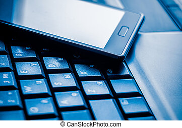 Computer keyboard and cellphone in a beautiful shade of blue