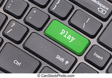 """Computer keyboard closeup with """"Play"""" text on green enter key"""