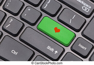 Computer keyboard closeup with red heart sign on green enter key