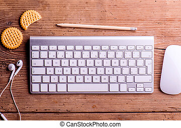 Computer keyboard, mouse, earphones, biscuits, pencil laid on de