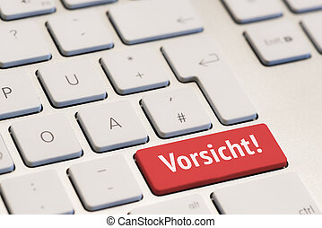 computer keyboard with the word vorsicht on red key