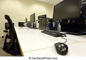 Computer lab room with empty workstation office desk and...