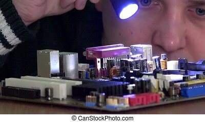 Computer main board inspected by technician man with flashlight