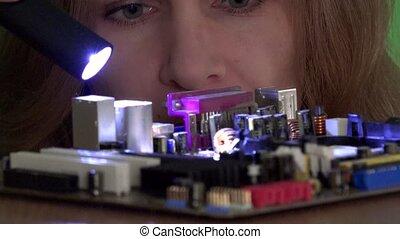 Computer main board inspected by technician woman with flashlight. Static closeup shot. 4K UHD