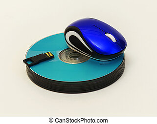 Computer mouse and USB flash lie on a stack of CD / DVD disk
