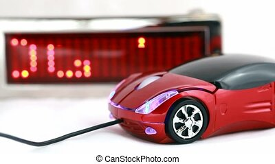 computer mouse in form of automobile lies beside informational LED display with word Technology