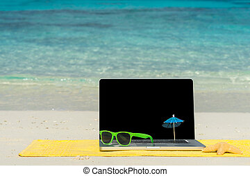 Computer notebook on beach - business travel background