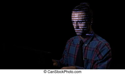 Computer programmer sitting in a dark room and typing while binary code is reflected on his face
