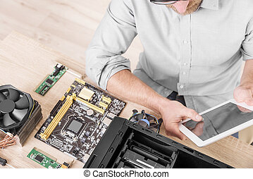 Computer repair professional. - Man using tablet pc during...
