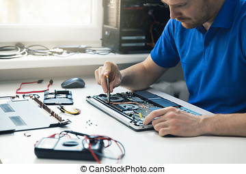 computer repair service - technician repairing broken laptop in office