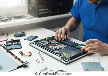computer repairman installing new hard disk drive in laptop