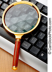 Computer security concept with keyboard and magnifying glass