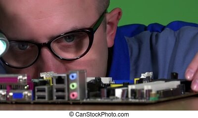 computer specialist man with glasses examining computer motherboard