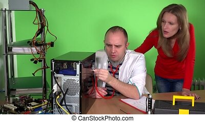 Computer specialist man with stethoscope examining pc and customer woman
