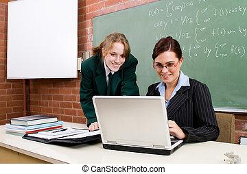 computer studies - happy teacher helping female student in...
