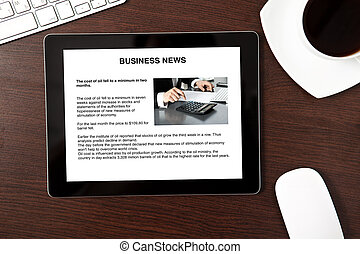 Computer tablet is on the table with business news on screen