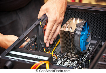 Computer technician installs cooling system of computer. Assembling PC