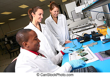 A team of computer technicians working on computer parts in the lab