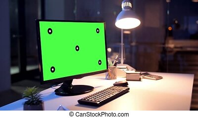 computer with green screen at night office - business,...