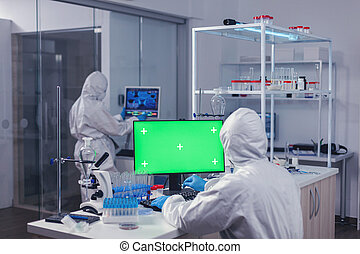 Computer with green screen in lab and medical staff